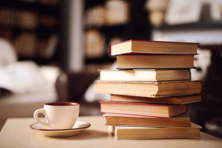 A stack of books with a coffee cup.